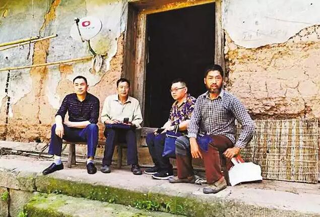杨骅(右二)生前在走访贫困群众。金鸡镇政府供图