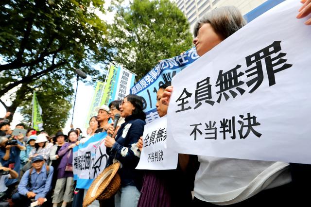 """""""福岛核事故起诉团""""在东京法院前,手举""""全员无罪 不当判决""""的纸张表示抗议(朝日新闻)"""