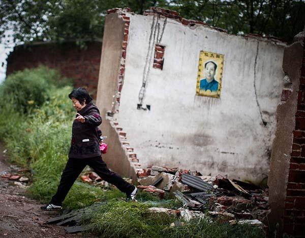2014年4月25日,湖南省衡东大浦镇,一位居民从一处破旧的房中跨出,由于离化工厂太近,多年前她从此地搬迁离开。 杨一 澎湃资料