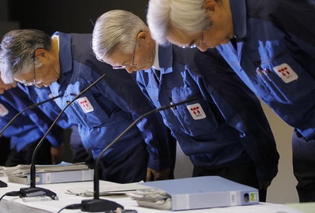 2011年3月30日,东电前高管胜俣恒久(中)、武藤荣(右)在东京出席新闻发布会前鞠躬。(新华社/美联)