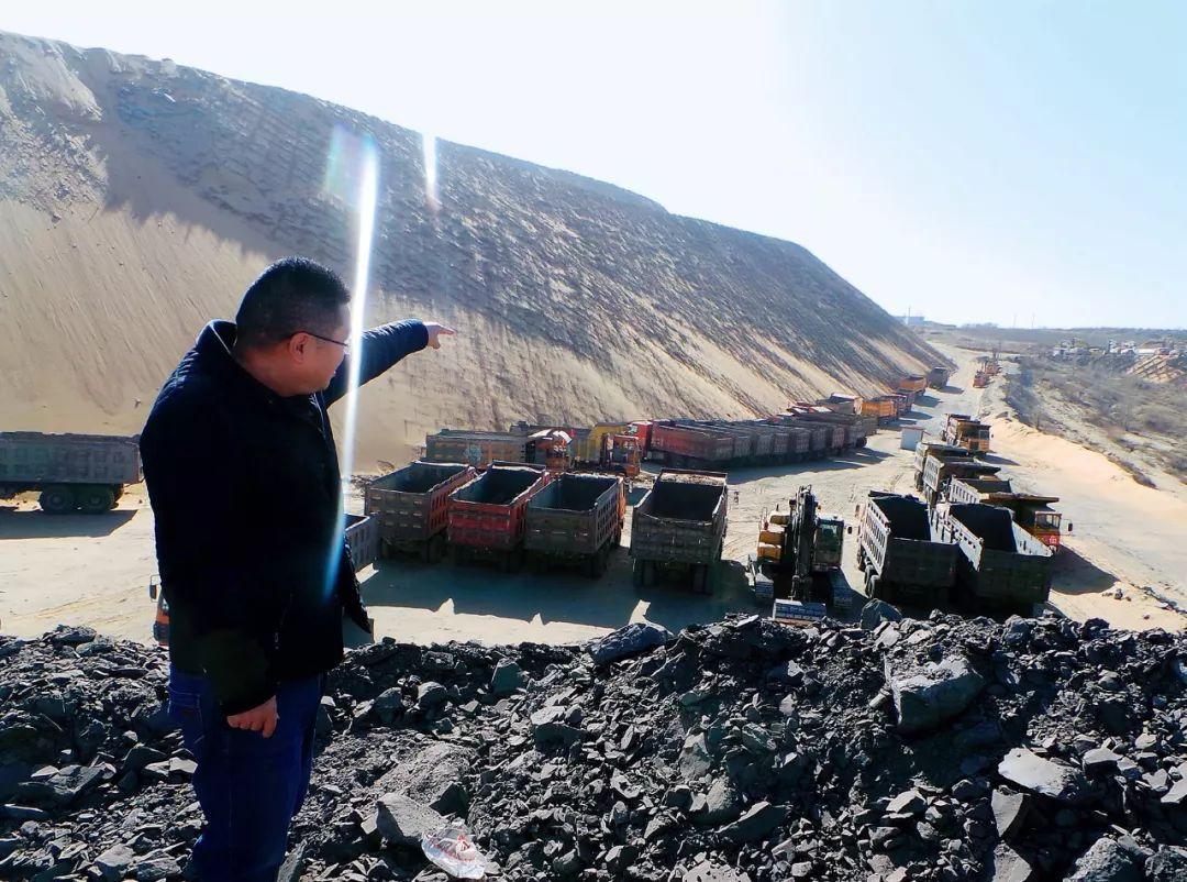 3月16日,神木考考赖沟综治项目负责人喻建林手指的方向,是滞留在工地上的五六十台渣土运输车、挖机等作业机器。摄影/本刊记者 周群峰