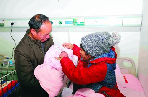 周应雄抱着刚出生的女儿舍不得放下。