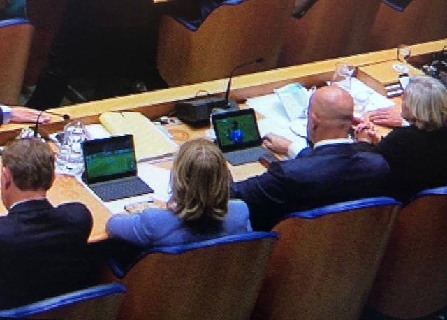 荷兰首相发言时,身后俩部长被拍到偷偷看球赛。(图源:荷兰一网)