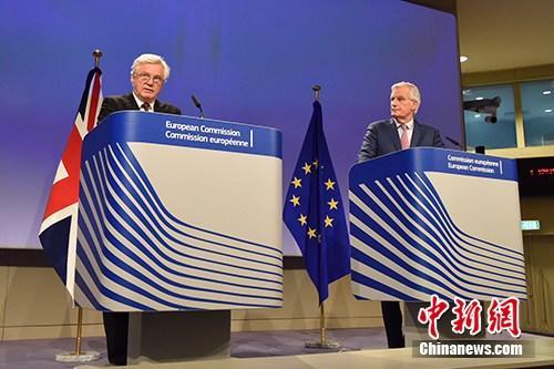 """当地时间2018年3月19日,脱欧谈判欧盟首席谈判代表巴尼耶(图右)与英国脱欧事务大臣戴维斯(图左)共见记者,宣布双方迈出""""决定性一步"""",就脱欧过渡期安排等议题达成协议,但棘手的英国北爱尔兰与爱尔兰边界问题仍悬而未决。中新社记者 德永健 摄"""