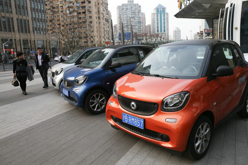 """资料图片:在上海曲阜路街头,行人经过路旁的""""共享汽车""""(2017年2月16日摄)。新华社记者 丁汀 摄"""