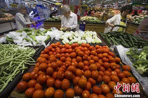 资料图?#22909;?#20247;在超市选购蔬菜。中新社记者 张云 摄