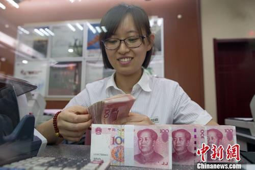 图为山西太原一银行工作人员正在清点货币。张云 摄