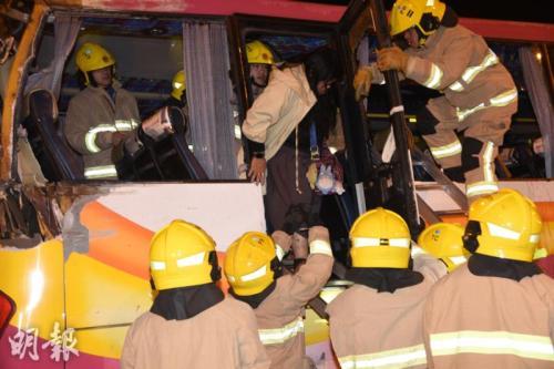消防员救出旅游巴士内伤者。图片来源:香港《明报》/蔡方山 摄