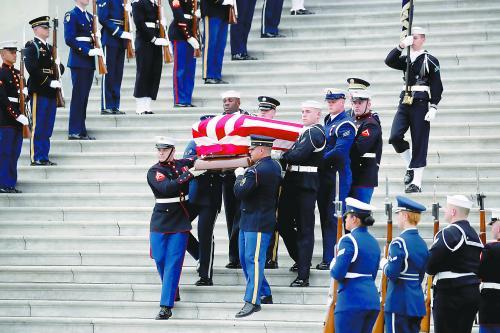 5日,美国前总统老布什的国葬仪式在华盛顿举走。图为仪仗兵将老布什的灵柩抬出国会大厦。