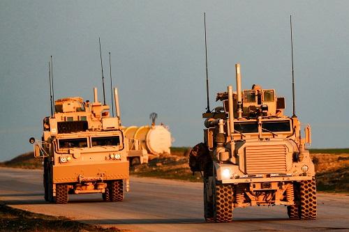 美军军车21日在叙利亚东北部哈塞克省的乡下走驶。(法新社)