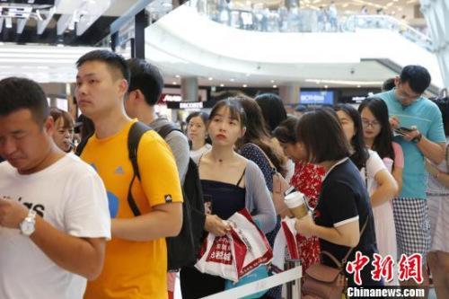 原料图:九月初三亚国际免税城店庆期间,顾客在列队购物。 王晓斌 摄