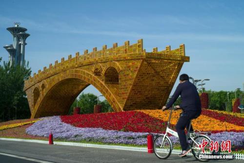 """資料圖:北京市民騎車經過北京國家會議中心前廣場的""""絲路金橋""""立體花壇。中新社記者 盛佳鵬 攝"""