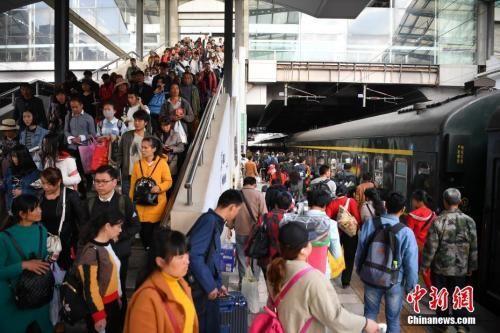 资料图:2018年3月12日,旅客在昆明火车站进站乘车。中新社记者 刘冉阳 摄
