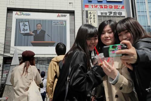 4月1日,在日本东京,行人在观看关于日本公布新年号的新闻节目时自拍。(新华社/法新)
