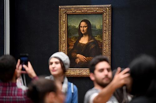 游客在巴黎卢浮宫的《蒙娜丽莎》画作前拍照。(法新社)