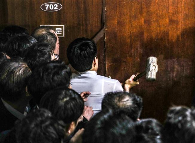 韩国执政党议员用铁锤砸门,进入国会会场。(韩国《中央日报》)