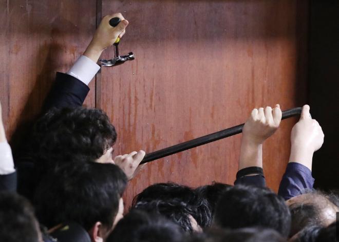 26日凌晨,韩国执政党议员试图用工具撬门,进入国会会场。(韩国《中央日报》)