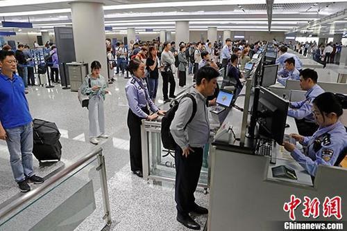 资料图:上海虹桥国际机场T1航站楼内入境大厅,民警正在为旅客办理通关手续。 中新社记者 殷立勤 摄