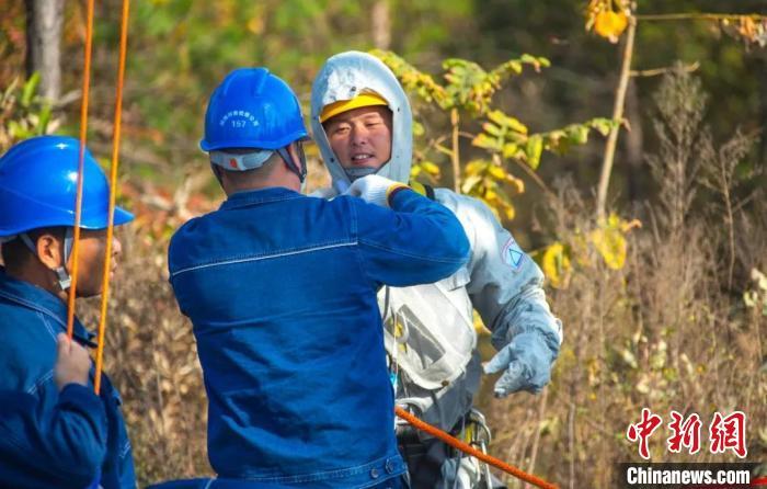 地电工作人员协助杨东辉做进入强电场开展带电作业准备 徐强 摄