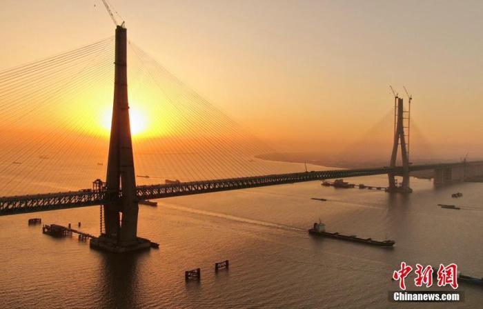 资料图:11月15日,沪通长江大桥主航道桥28号墩完成了最后一组斜拉索吊装,标志着沪通长江大桥全桥斜拉索吊装全部完工。沪通长江大桥由中铁大桥局承建,全长11072米,主桥采用双塔斜拉桥设计,主跨1092米。建成后将成为沿海重要的铁路、公路过江通道,在进一步完善区域交通运输结构、提高过江通道运输能力、促进长三角经济社会一体化等方面具有重要意义。 许丛军 摄