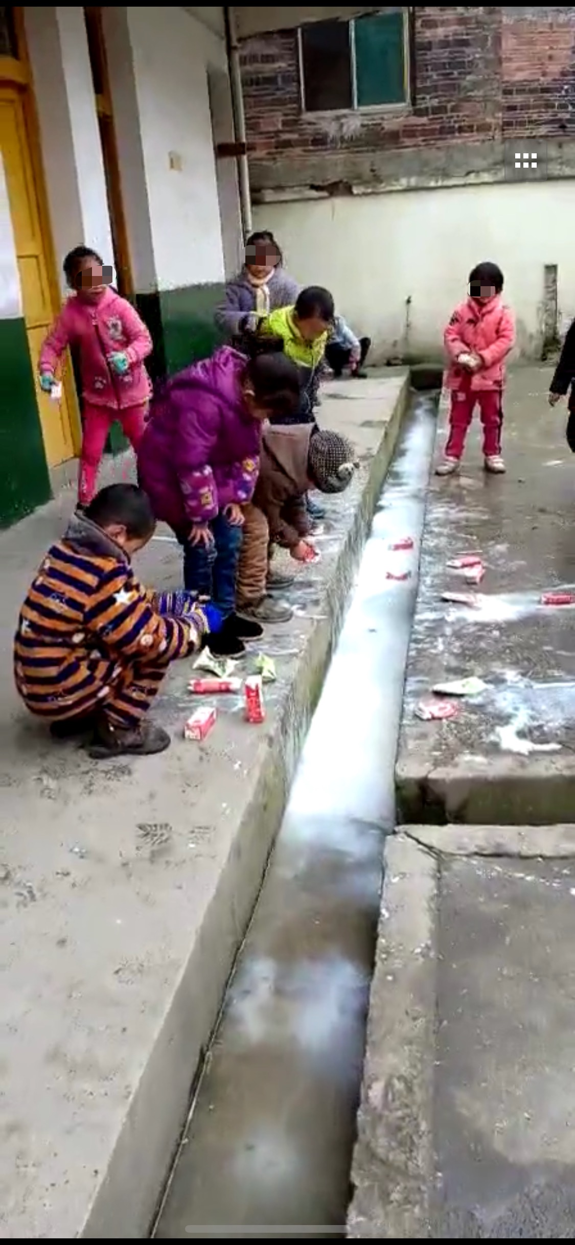 数名小学生蹲在教室外,将手中的牛奶倒入走廊边的水沟。来源:视频截图