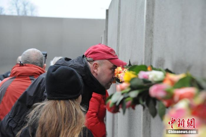 (图二)资料图:2014年,柏林民众自发前往柏林墙遗址,纪念这段历史。纪念场的一段柏林墙内,象当年一样,民众只能透过墙上的缝隙窥探墙外的世界。中新社发 黄霜红 摄