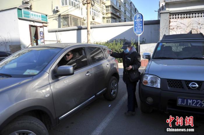 北京市某停车场管理员为车主指挥倒车。中新网记者 金硕 摄