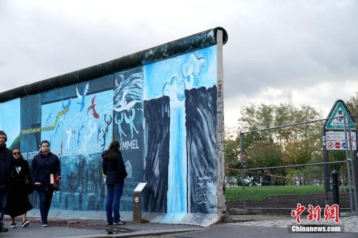 """(图一)2019年11月4日下午,游人经过在柏林墙遗址基础上形成的""""东边画廊""""。中新社记者 彭大伟 摄"""