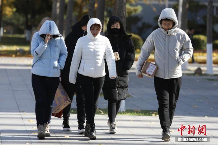 资料图 市民在寒风中出行 中新社记者 蒋启明 摄