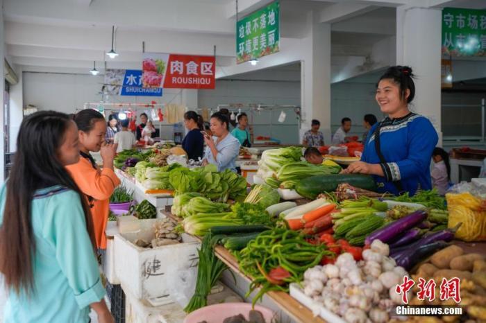 贵州省榕江县易地扶贫搬迁安置点卧龙小区,侗族妇女石本艳在菜市场卖菜。中新社记者 贺俊怡 摄