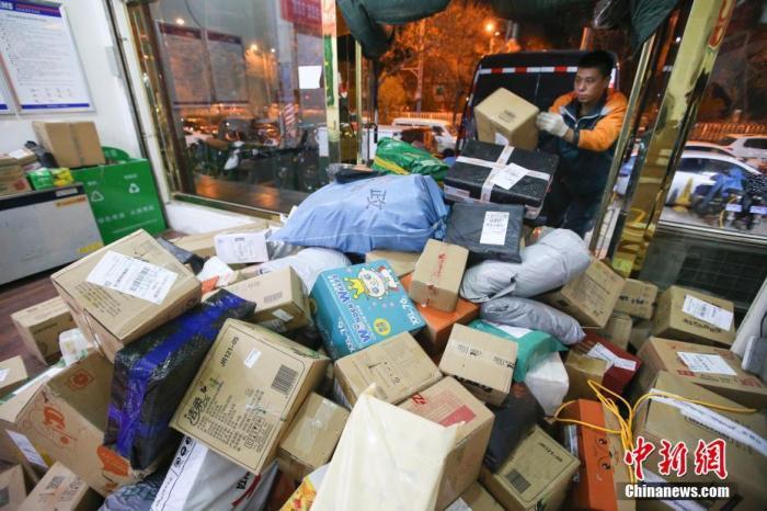 11月13日,山西太原的物流业工作人员加紧给快递卸车。中新社记者 张云 摄
