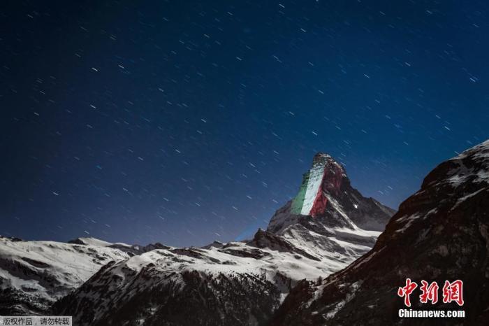 """资料图:当地时间4月1日,瑞士阿尔卑斯山脉标志性的马特洪峰出现灯光投影的巨大横幅,在疫情中呼吁""""希望和团结""""。图为灯光在马特洪峰山顶映出意大利国旗。"""