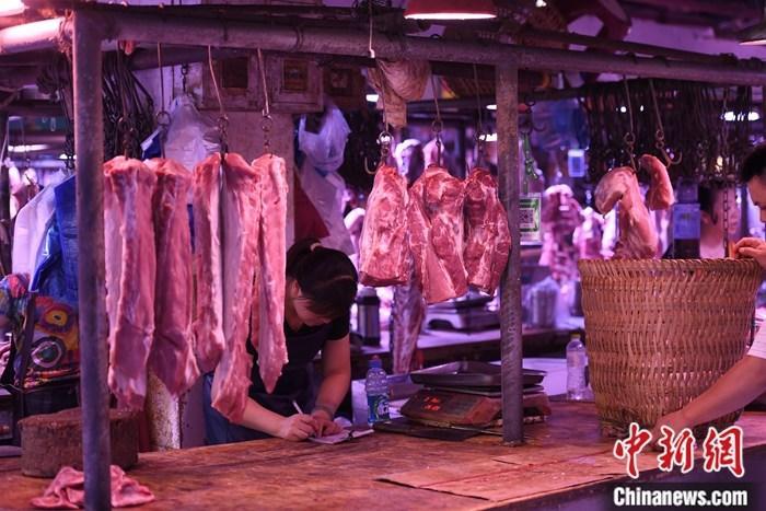资料图为重庆一农贸市场内的商家挂满充足的猪肉。中新社记者 陈超 摄