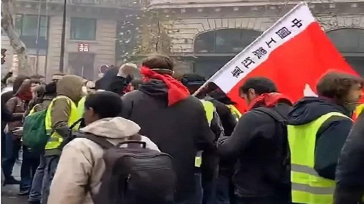 """▲在荟萃于奥斯曼大街的一群示威者中,有人打出""""中国工农红军""""旗帜。图/欧洲时报微博视频截图"""