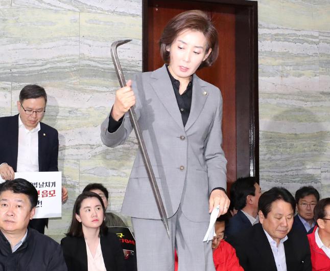 """自由韩国党党鞭展示撬棍,怒斥""""暴力""""。(韩国《中央日报》)"""