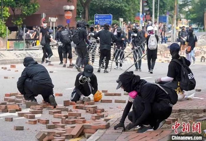 11月14日下昼,多多蒙面暗衣人在香港理工大学对出的畅运道设立路障,发掘人走道上的砖块阻滞道路。中新社记者 张炜 摄