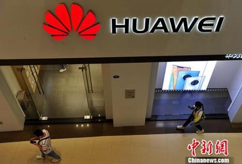 原料图:市民从华为产品专卖店旁通过。 中新社记者 张斌 摄