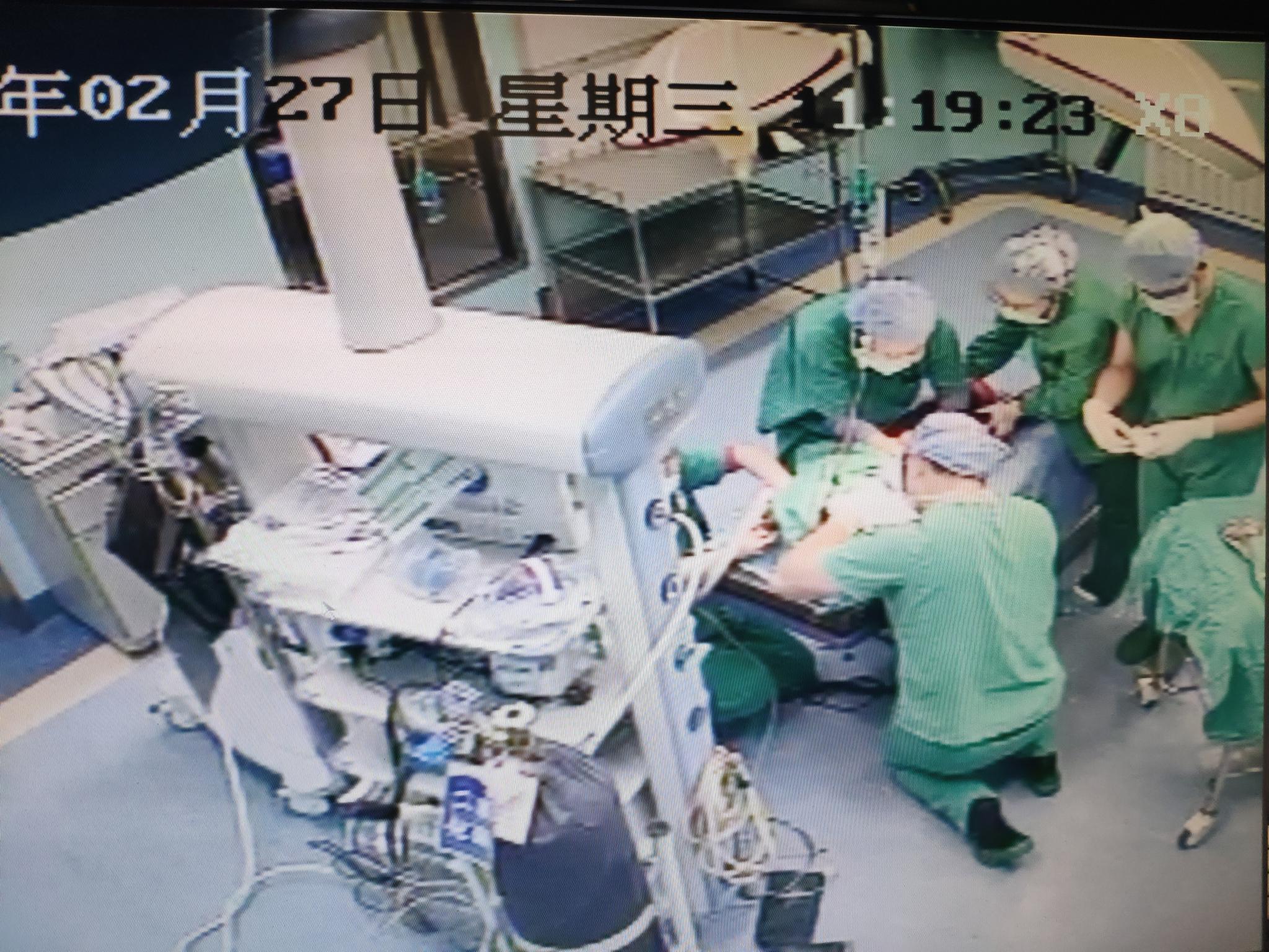 湖北武汉汉阳医院神经外科医生雷丹跪在地上为小患者做手术。受访者供图