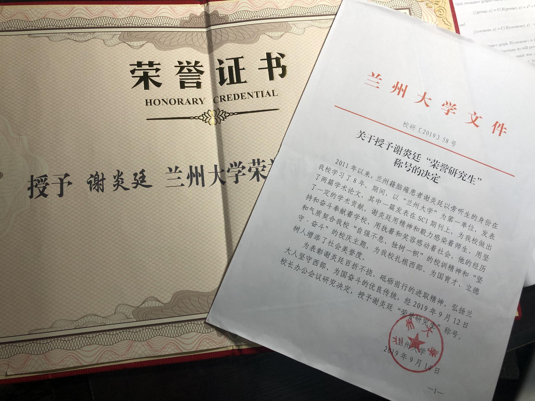 """兰州大学授予谢炎廷""""荣誉研究生""""的文件和奖状。新京报记者王瑞锋 摄"""