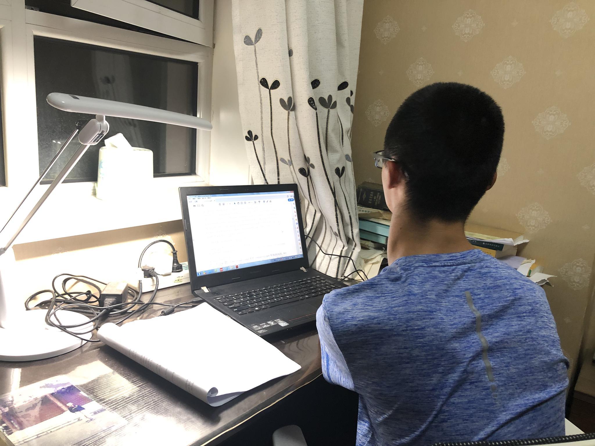 9月24日晚,谢炎廷在卧室里用电脑写论文。新京报记者王瑞锋 摄
