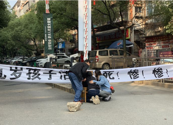 ▲11月8日上午,罗鸣妈妈趴在小区门口儿子的遗像前。新京报记者 付子洋 摄