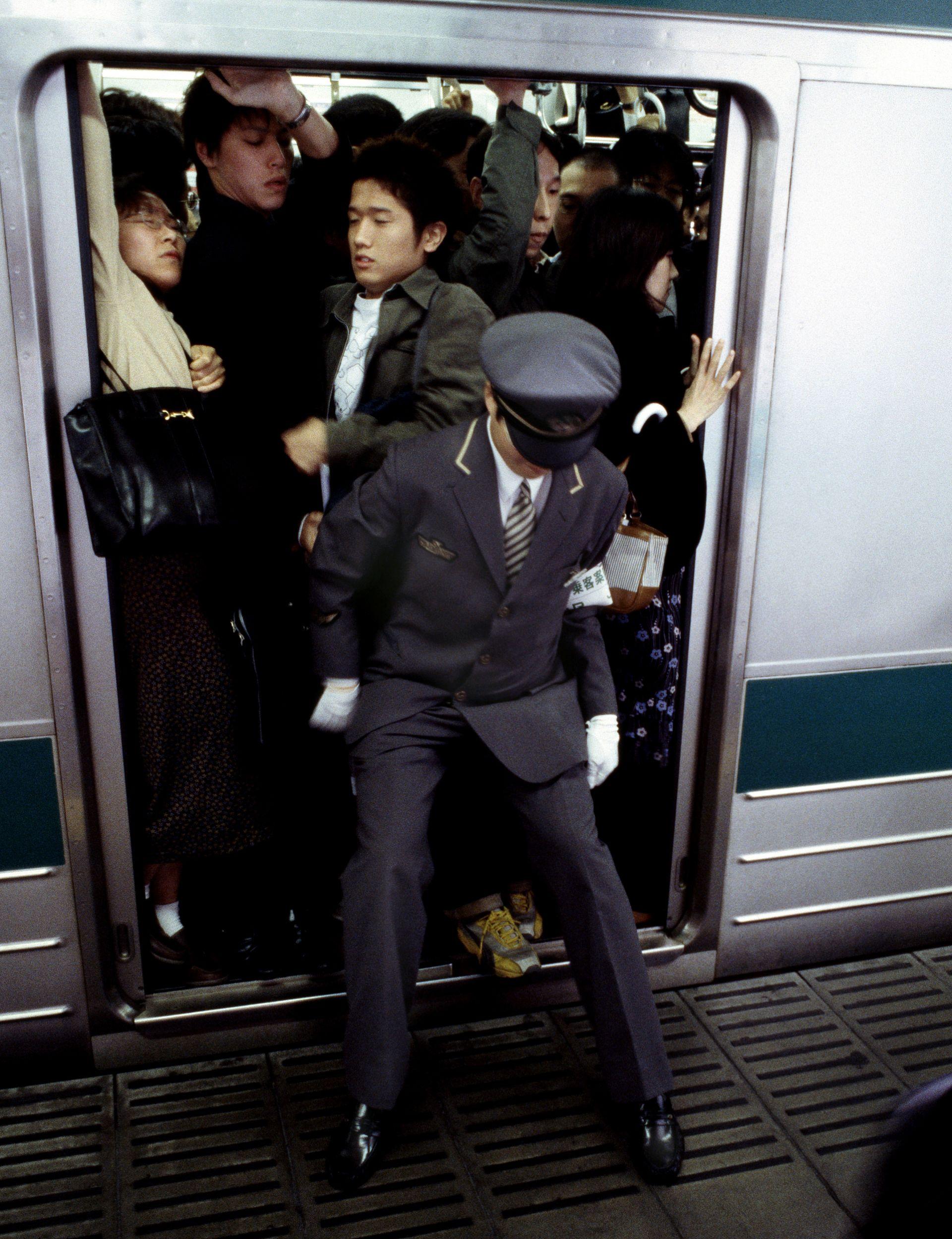 (東京地鐵早晚高峰乘客靠列車員硬塞才能擠進車廂,圖片來源:視覺中國.圖片