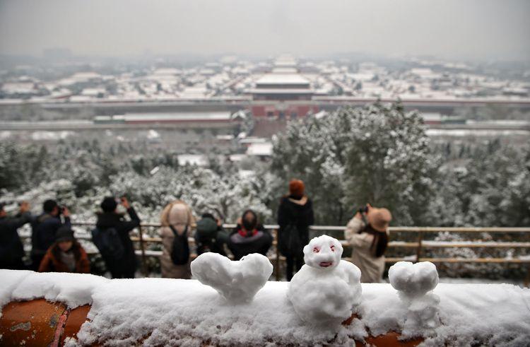 """一个幼雪人旁陪同着两个""""心""""。"""