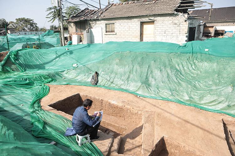 2019年10月20日,正在挖掘的古墓现场,考古工作人员正在对古墓信息进行记录。
