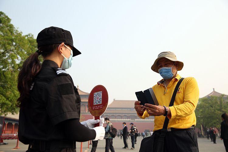"""观众在午门广场扫""""健康码""""。摄/新京报记者 浦峰"""
