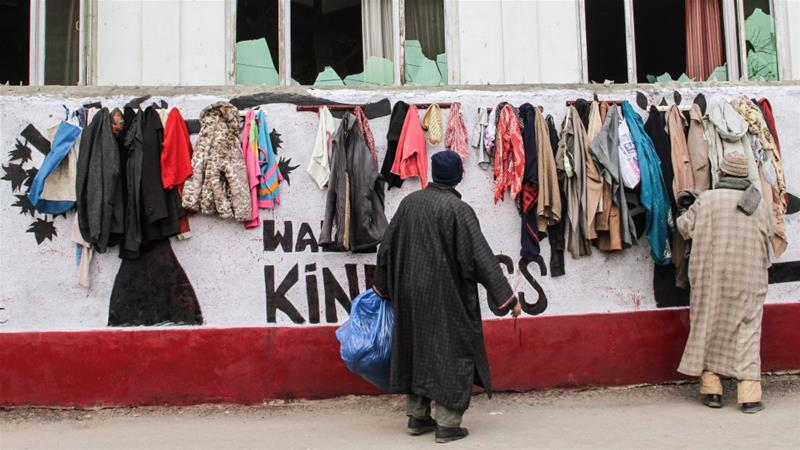 两名外子在挑选墙上衣物