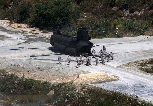 2011年9月30日,在韩国抱川的一个军事训练基地,参添军演的美军士兵从一架军用直升机中走出。 新华社发