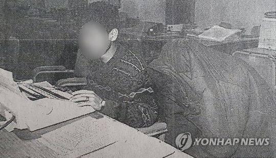 被锁定为华城案真凶的李某(右)1994年因涉嫌奸杀妻妹在警署蒙头接受讯问。 韩联社