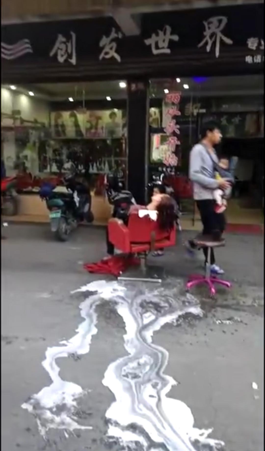 烫染店外,一女子后抬在椅子上。视频截图