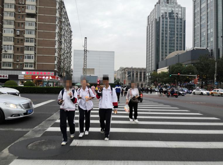 三位弟子议决路口时玩手机